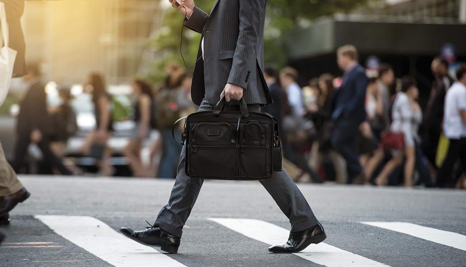 Business executive crossing the street using smatphone showing threat of BEC scams