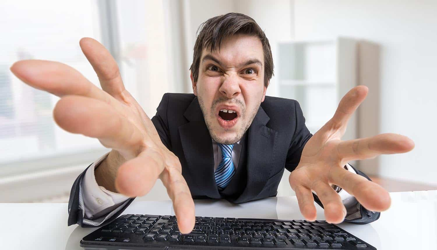 Confused angry businessman working with computer showing need for security not to hold back productivity