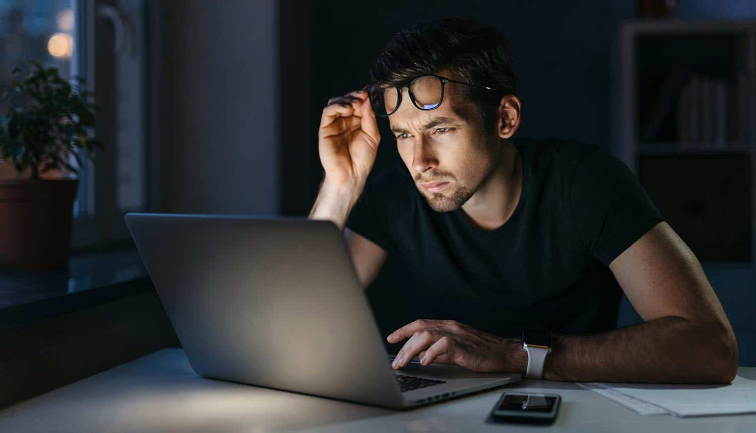 Man holding glasses while starting at laptop showing challenges of misinformation