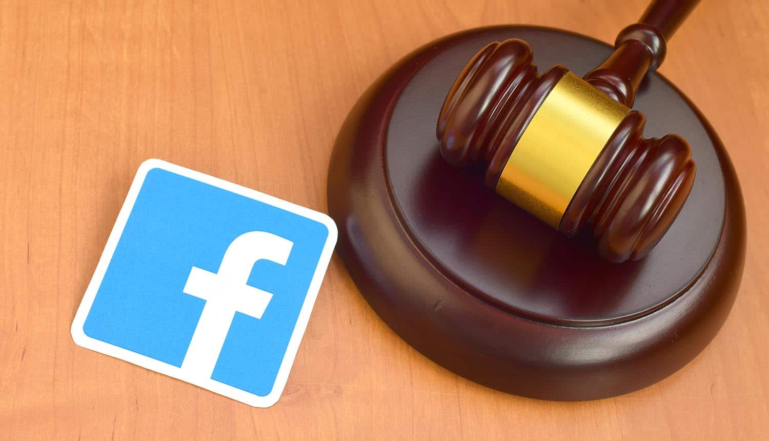 Facebook paper logo lies with wooden judge gavel showing privacy violation of user consent