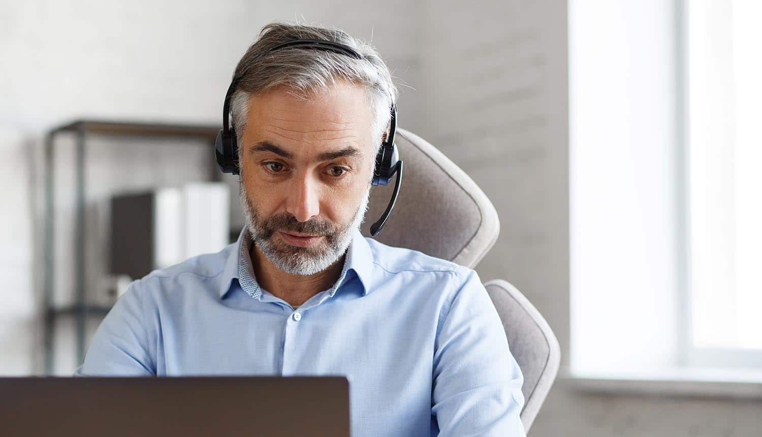 Grey-haired senior man using collaboration communications tools while remote working