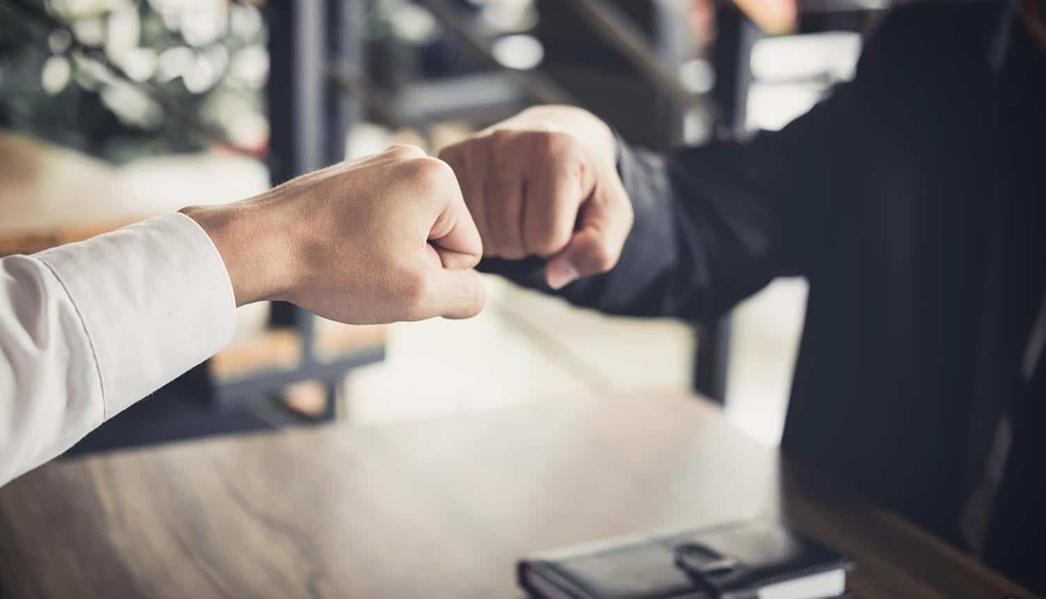 Businessmen giving fist bump showing trust in Zero Trust