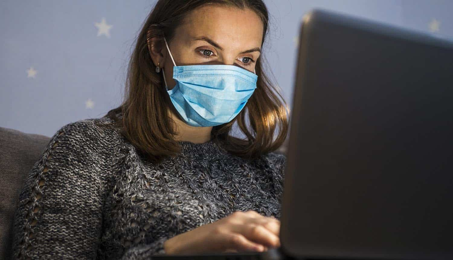 Young business woman in medical mask working from home showing impact of remote working on identity management
