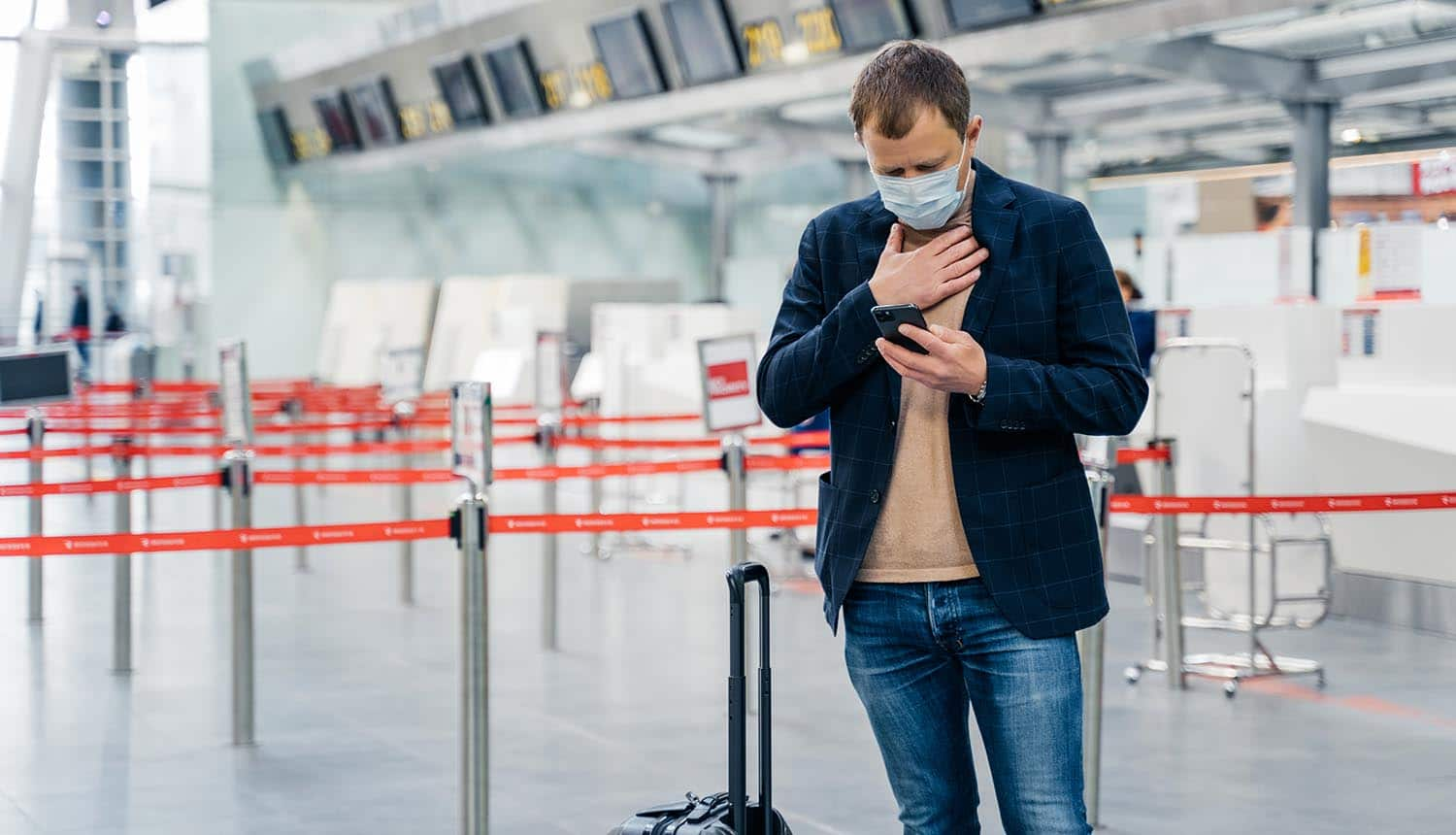 Businessman walks in airport terminal showing potential immunity passports as COVID vaccine rolls out