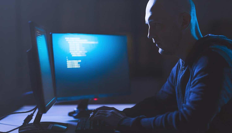Male hacker in dark room planning cyber attack showing hacking group release of stolen user credentials on hacker forum