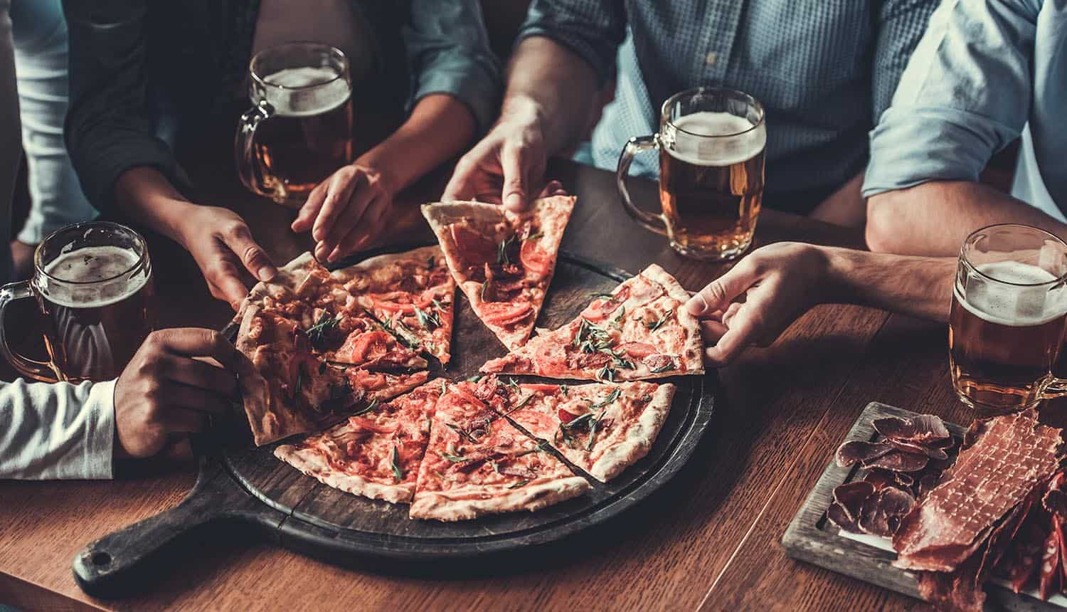 Friends sharing pizza showing WhatsApp privacy policy allowing data sharing with Facebook