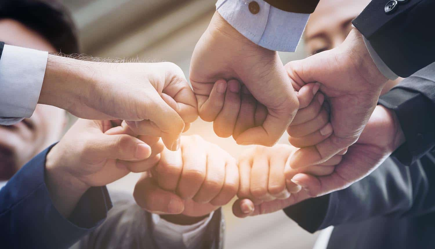 Business team joining hands showing teamwork and success