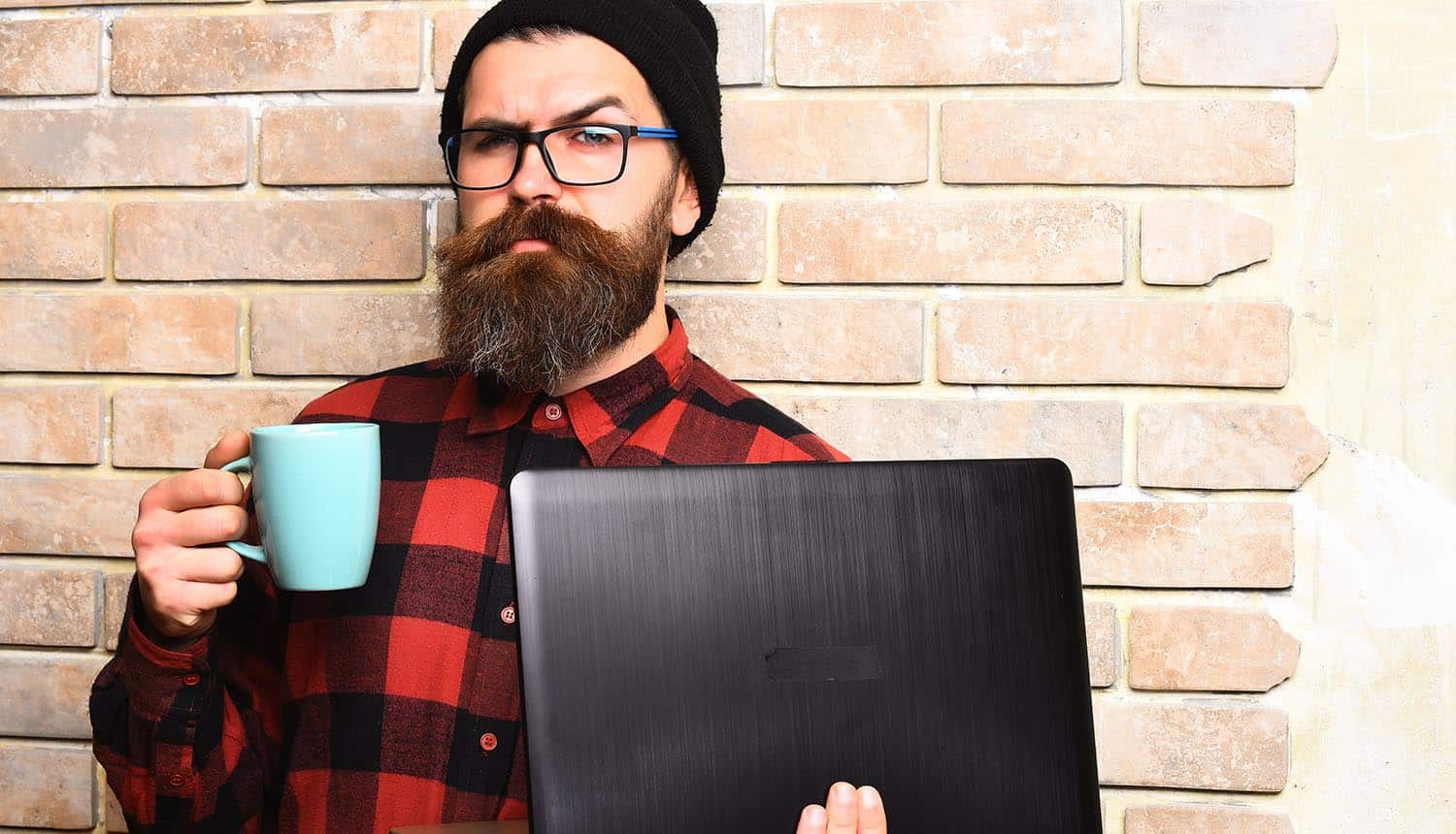 Serious unshaven developer holding laptop showing No Code and Low Code security risks