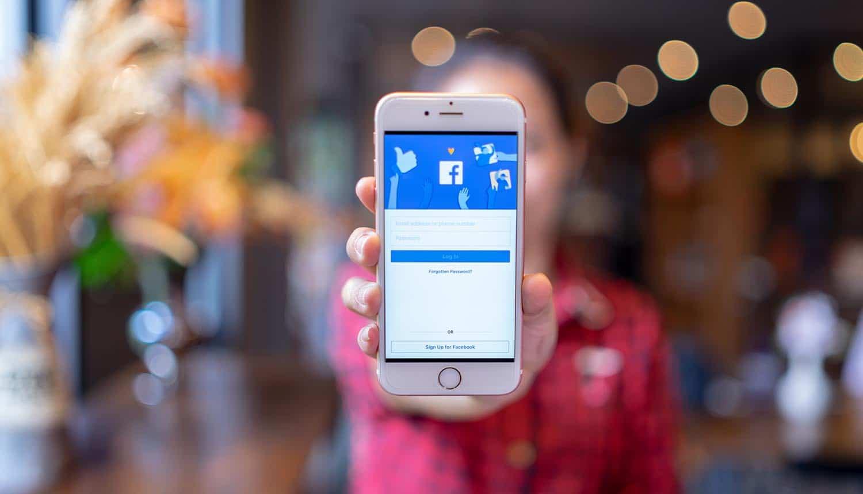 Woman holding mobile phone showing Facebook user data exposed via Telegram bot