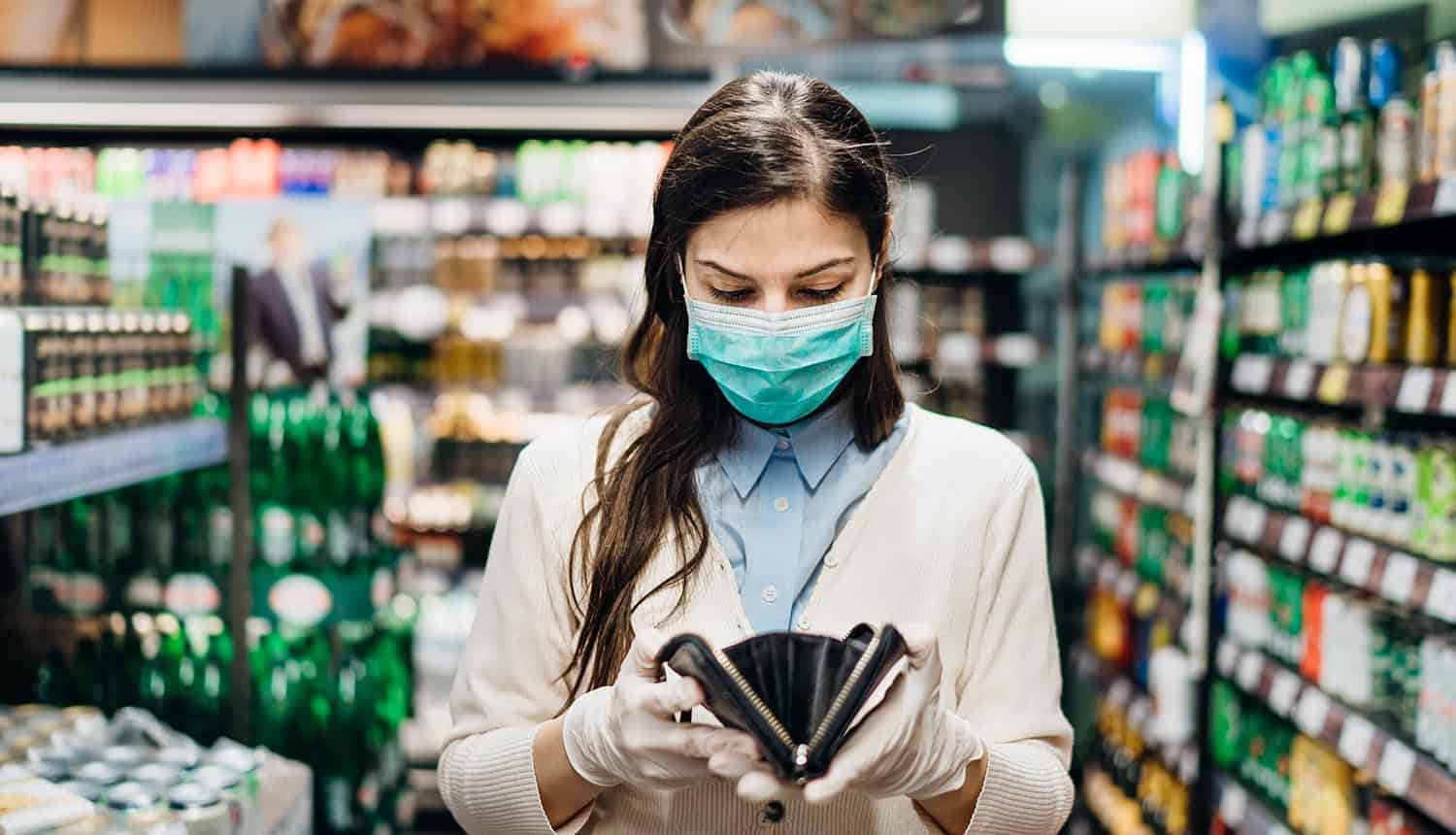 Worried woman with mask groceries shopping in supermarket looking at empty wallet showing identity theft during pandemic