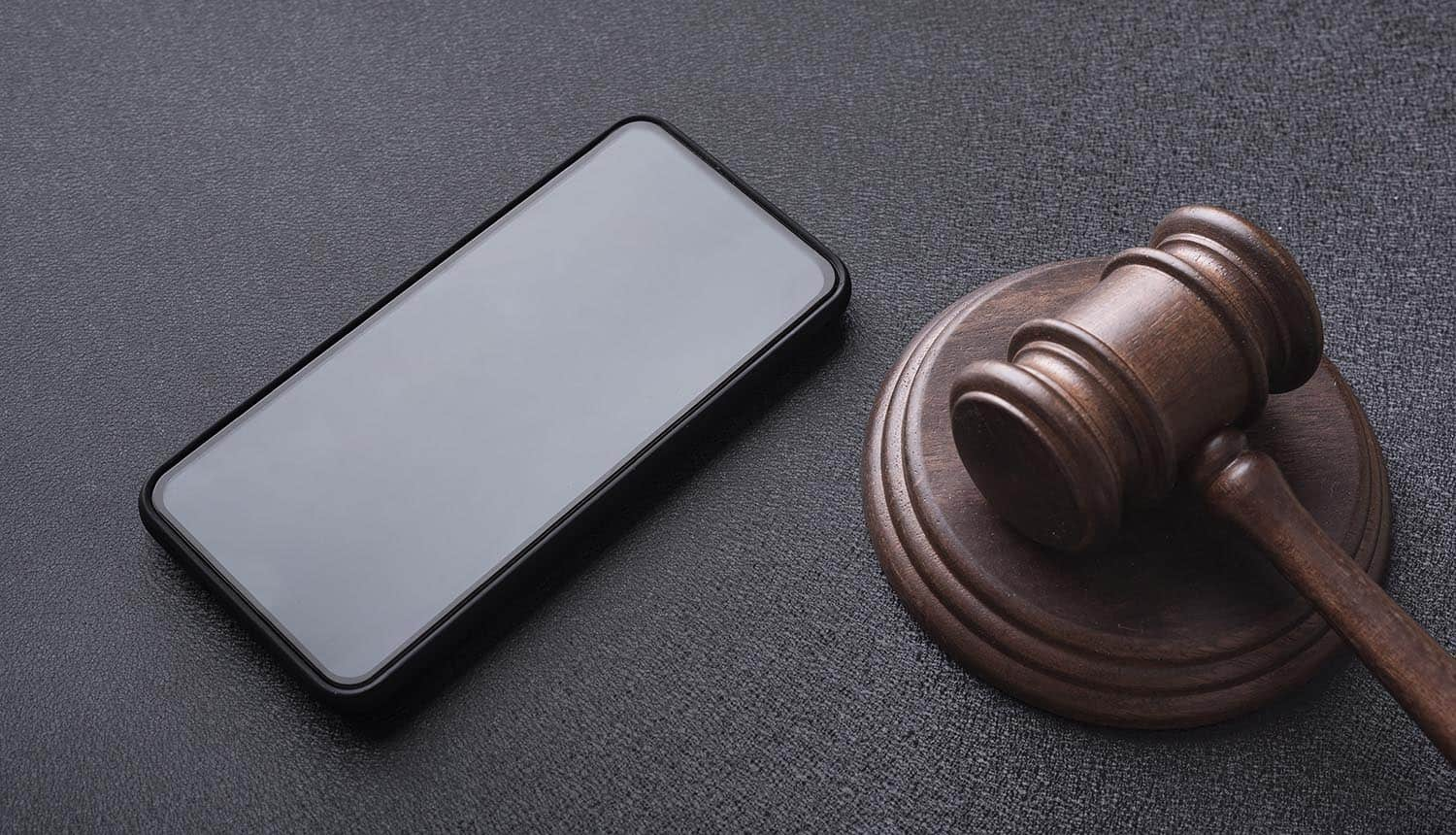 Smartphone and judges gavel on table showing technology risks