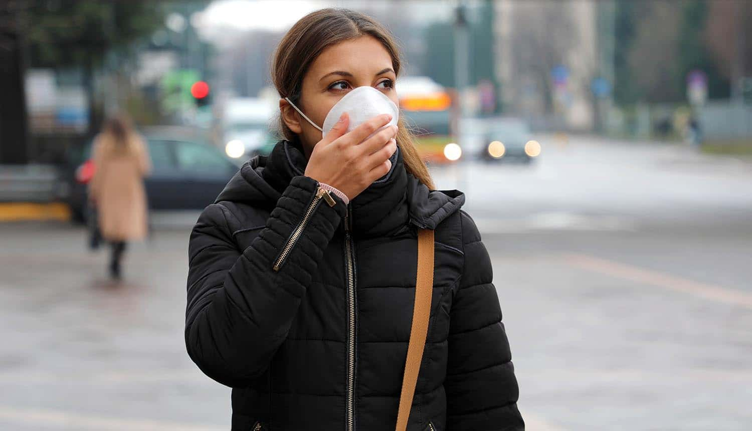 Woman in city street wearing face mask protective for COVID-19 showing trends for new normal