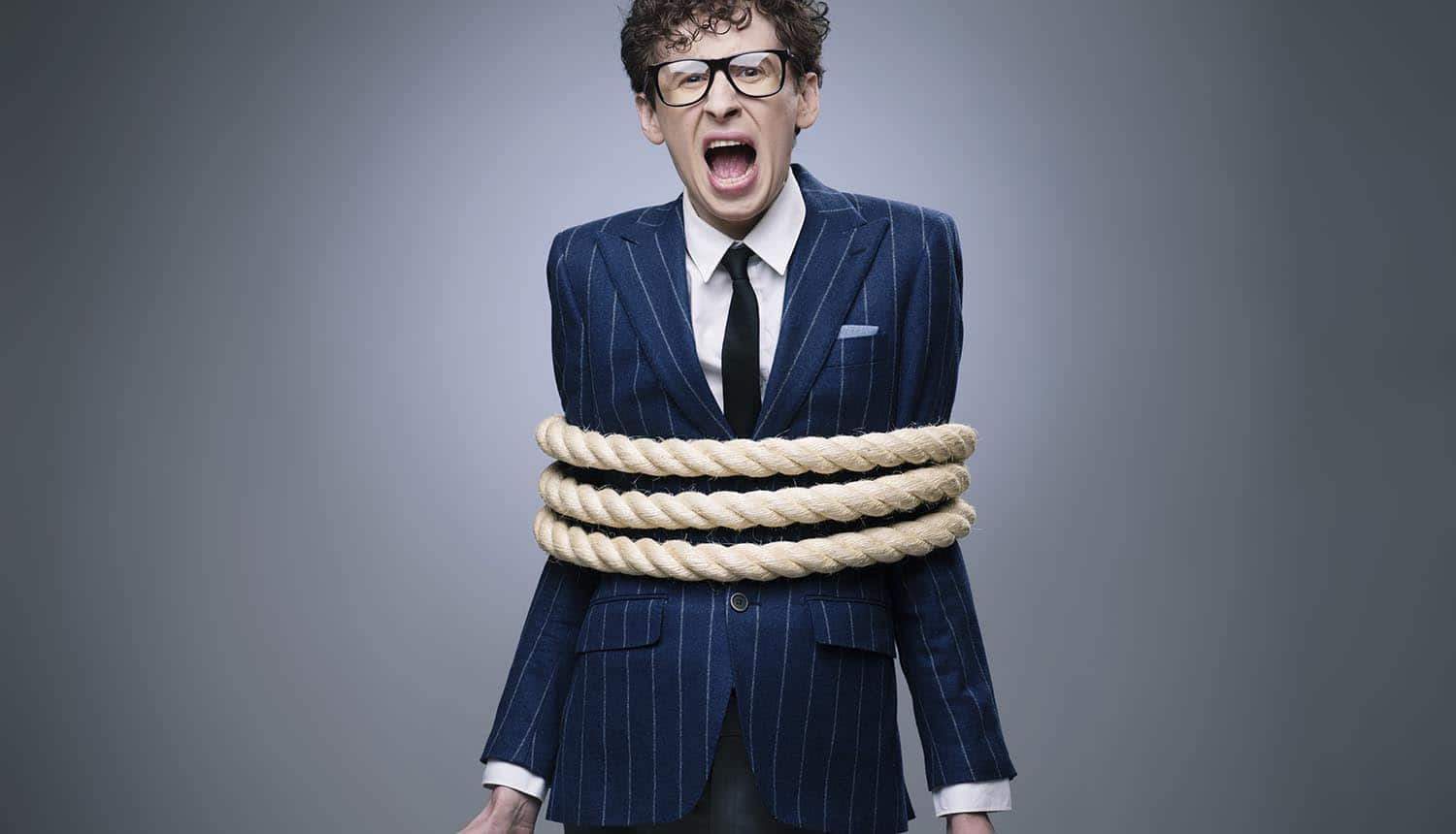 Business man tied up with rope screaming for help showing threat of ransomware attacks