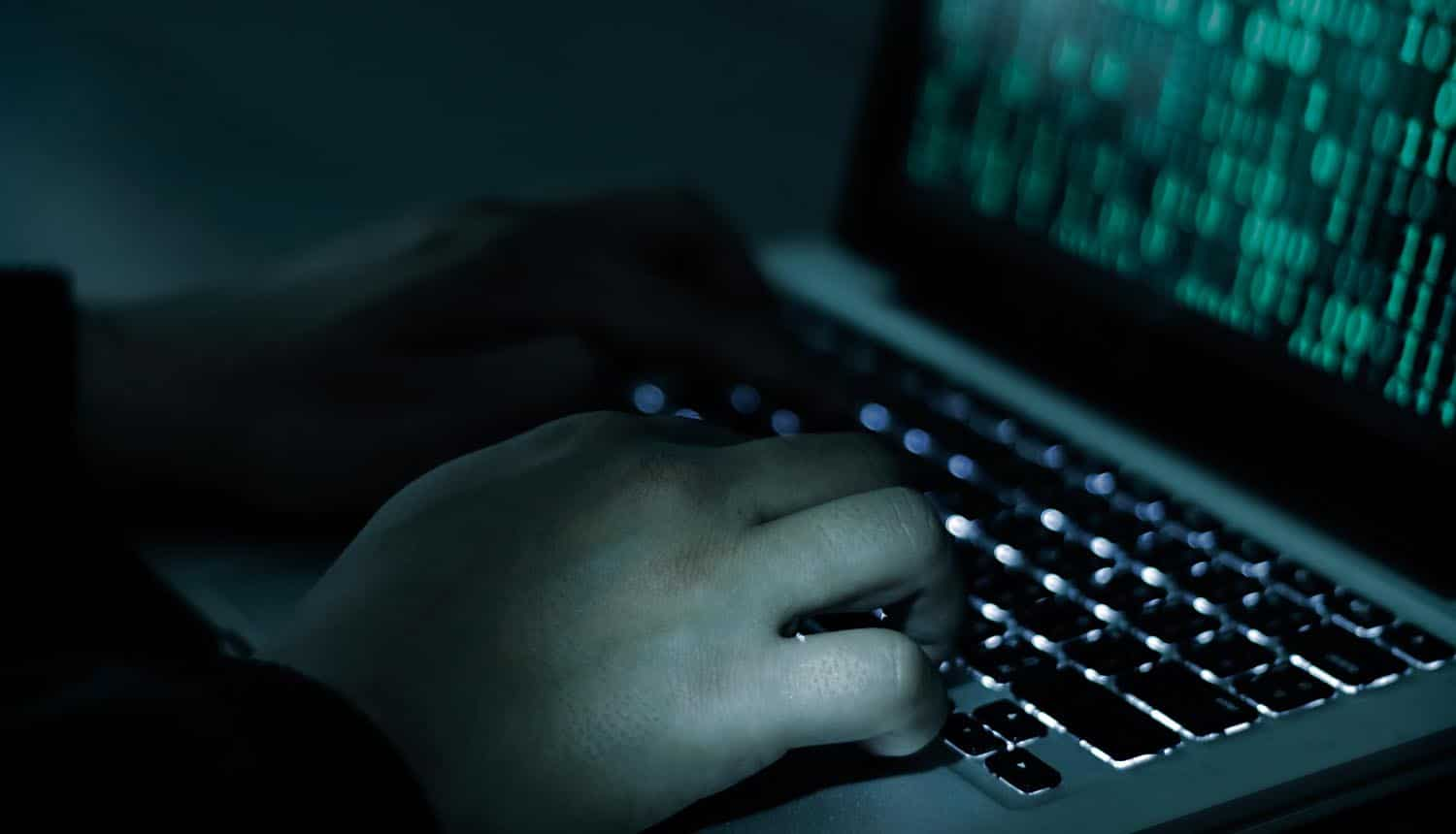 Hacker hands with binary codes on monitor showing the dark web