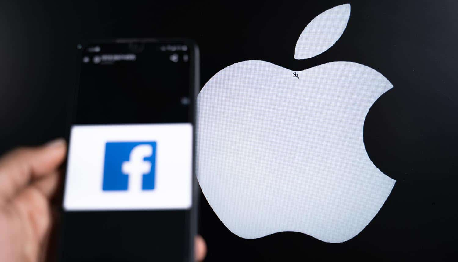 Facebook app on phone and apple on background display showing battle over IDFA tracking