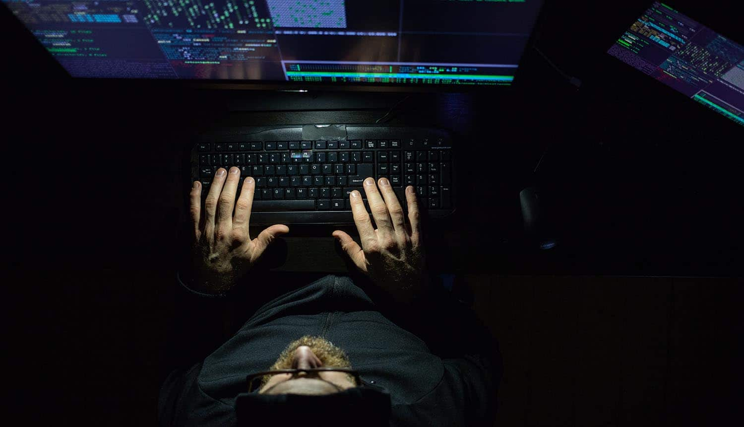 Hacker working at night showing suspected ransomware attack
