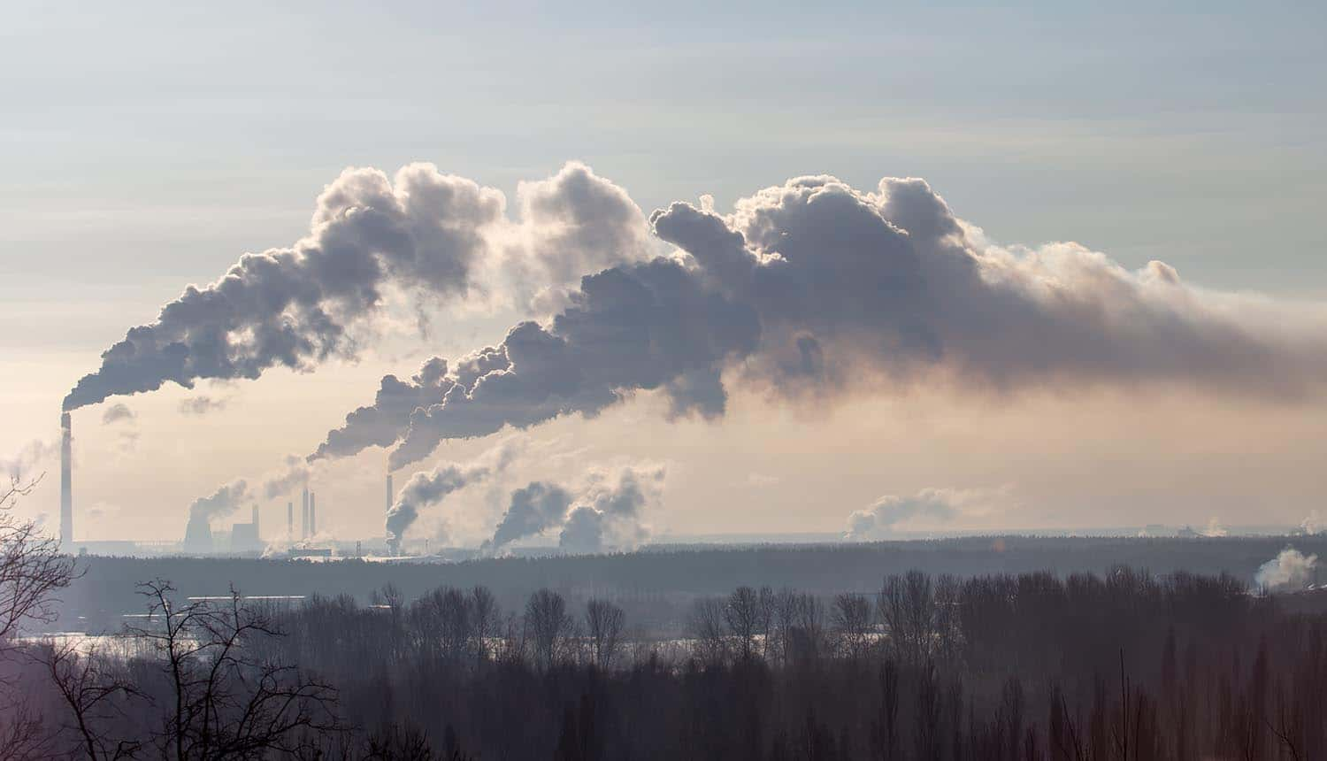 Smoke from the chimneys of a plant showing need for industrial cybersecurity