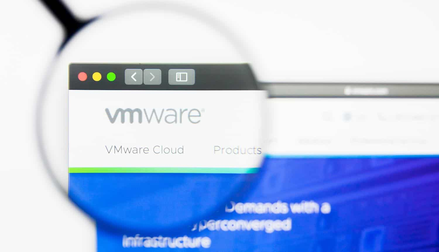 Magnifying glass over VMware website showing security bug affecting VMware servers