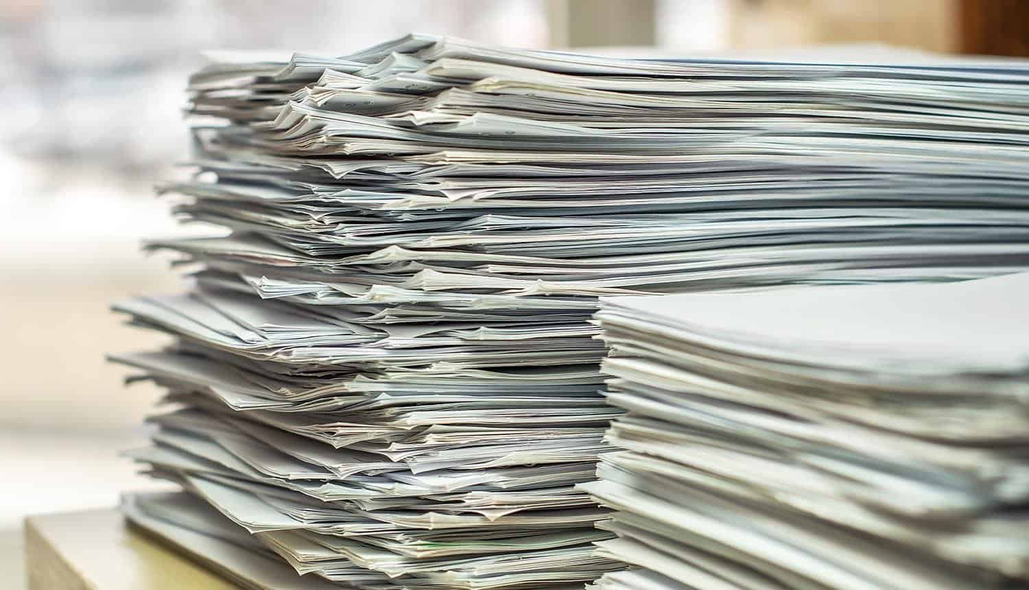 Bundles bales of paper documents showing risk of document metadata to reconnaissance