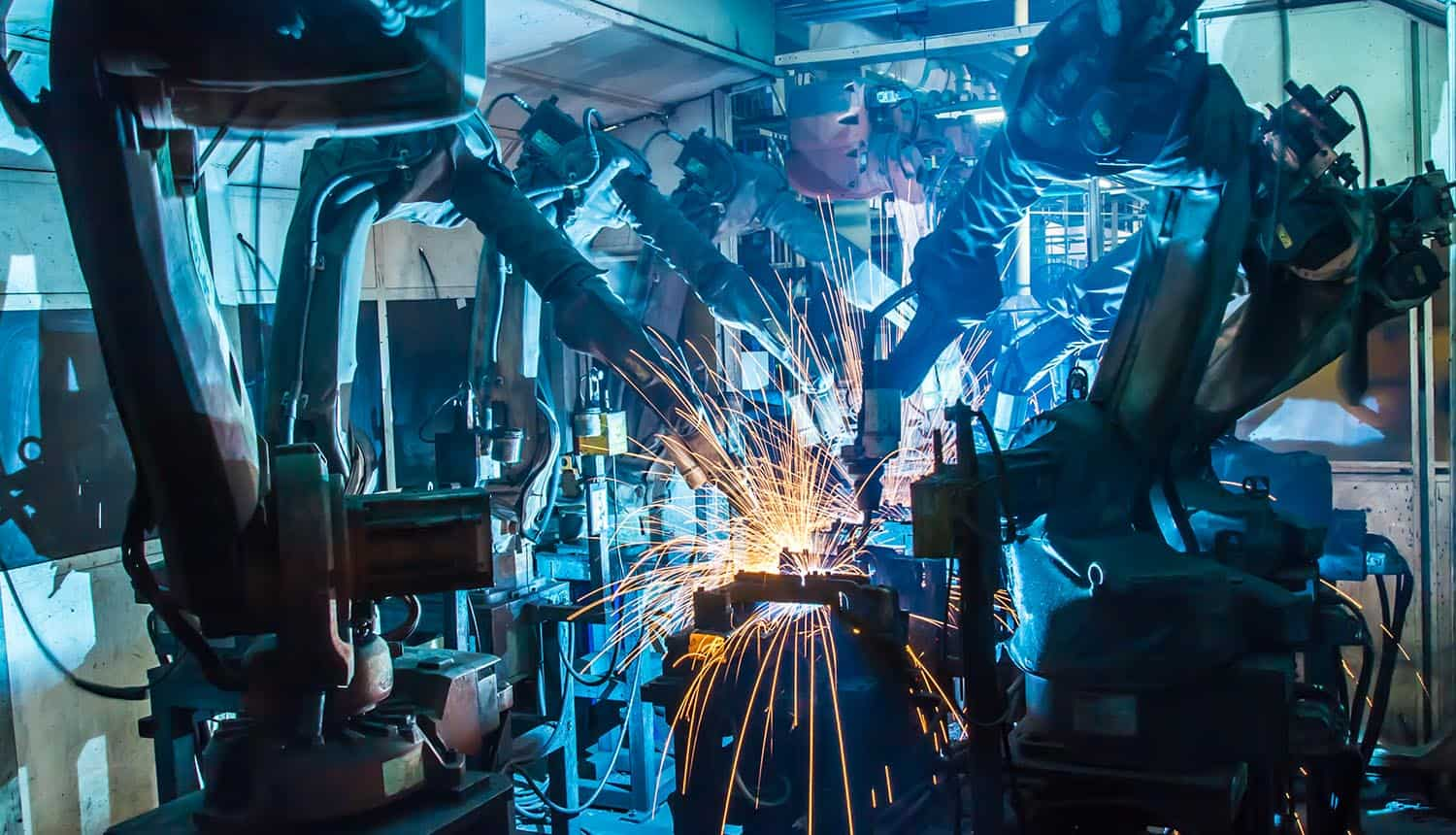 Robots welding movement in a car production factory showing IoT security and zero trust