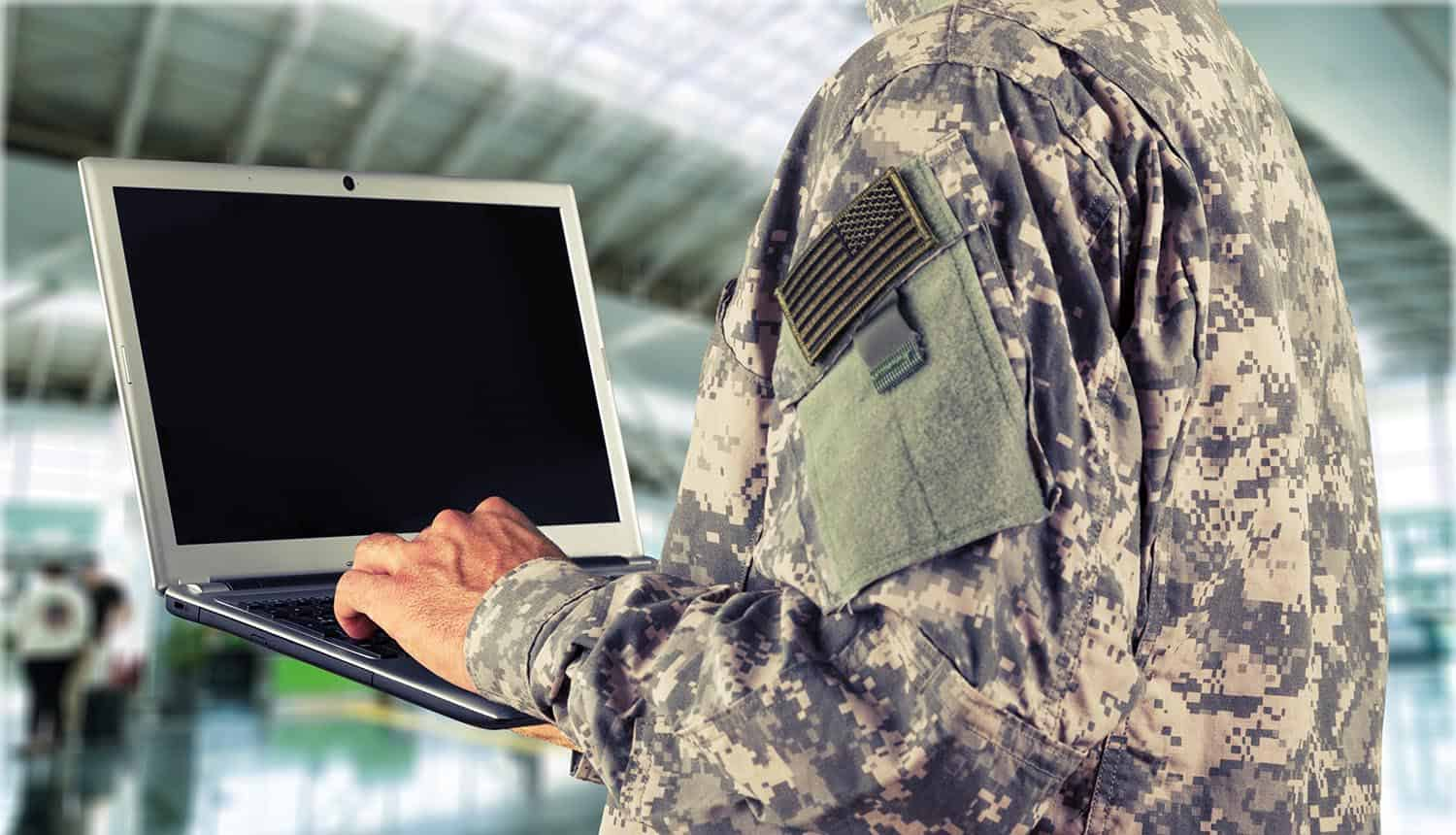 Military soldier holding laptop showing MSP compliance with CMMC framework