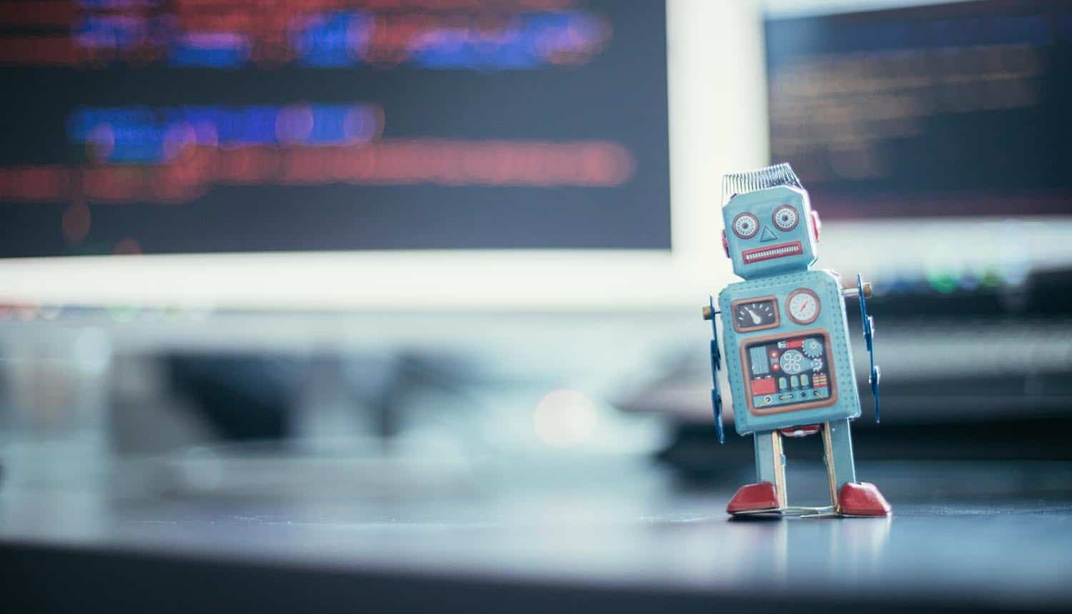 Toy robot in front of screens with program code showing bot traffic