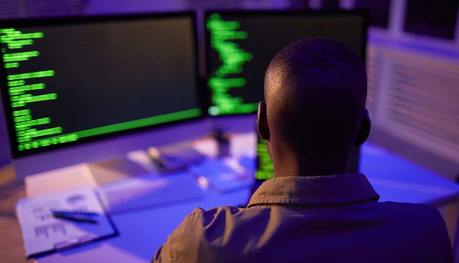 Rear view shot of developer sitting in front of monitors showing Codecov supply chain attack