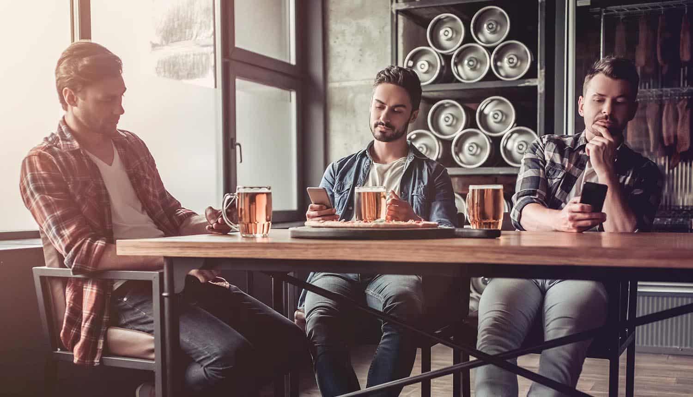 Three men in bar with smartphones in hands showing challenges with DevSecOps