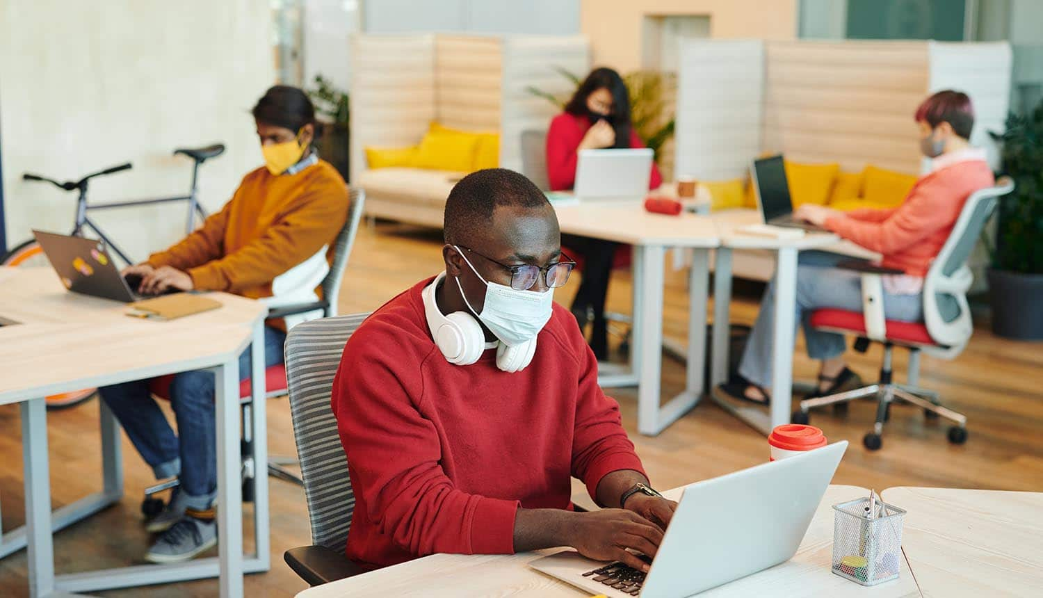 Male office manager in casualwear and protective mask using laptop showing workplace safety during pandemic