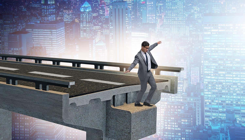 Businessman in uncertainty with broken bridge