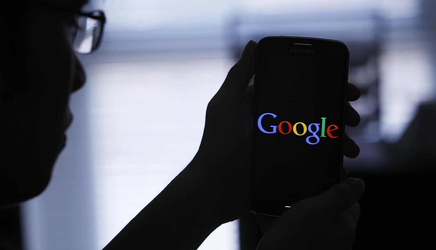 Young man holding up smartphone with Google logo showing ad tracking on Android
