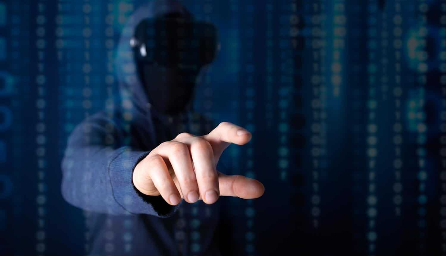 Hacker with hands reaching out showing piracy and need to prevent data loss