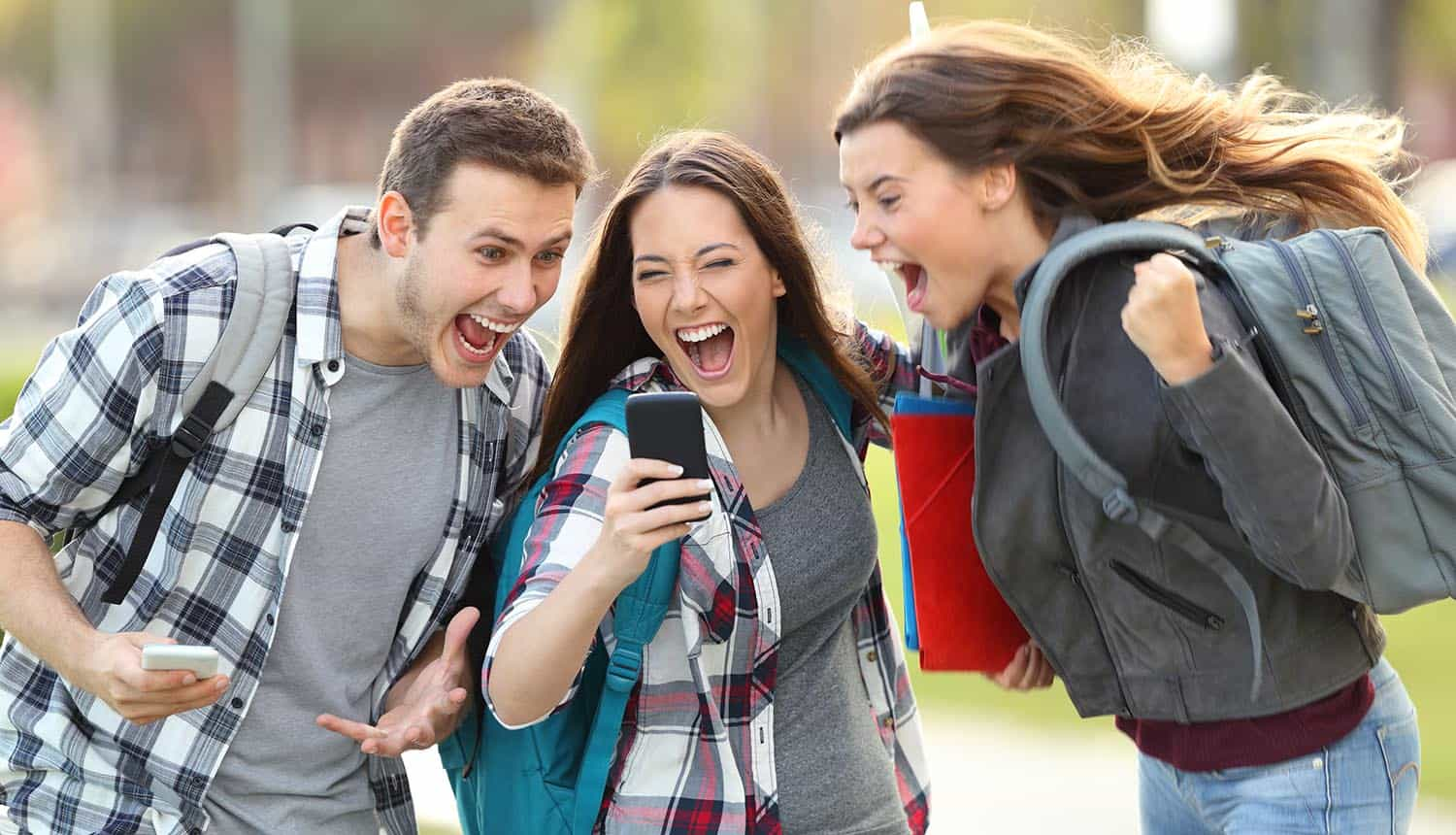 Front view of three excited young people receiving good news
