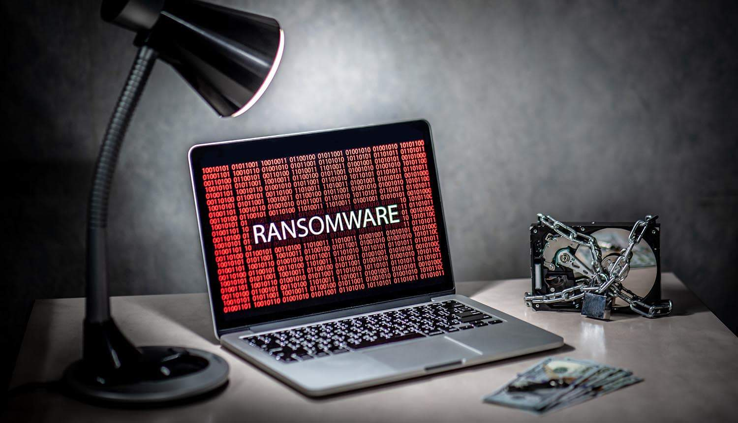 Hard disk file locked by chain and padlock with binary ransomware on laptop monitor showing ransomware payments