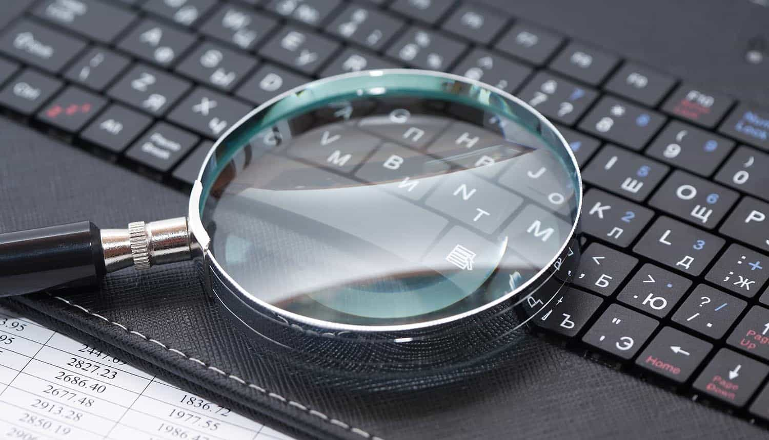 Magnifying glass on black laptop keyboard showing compliance audits
