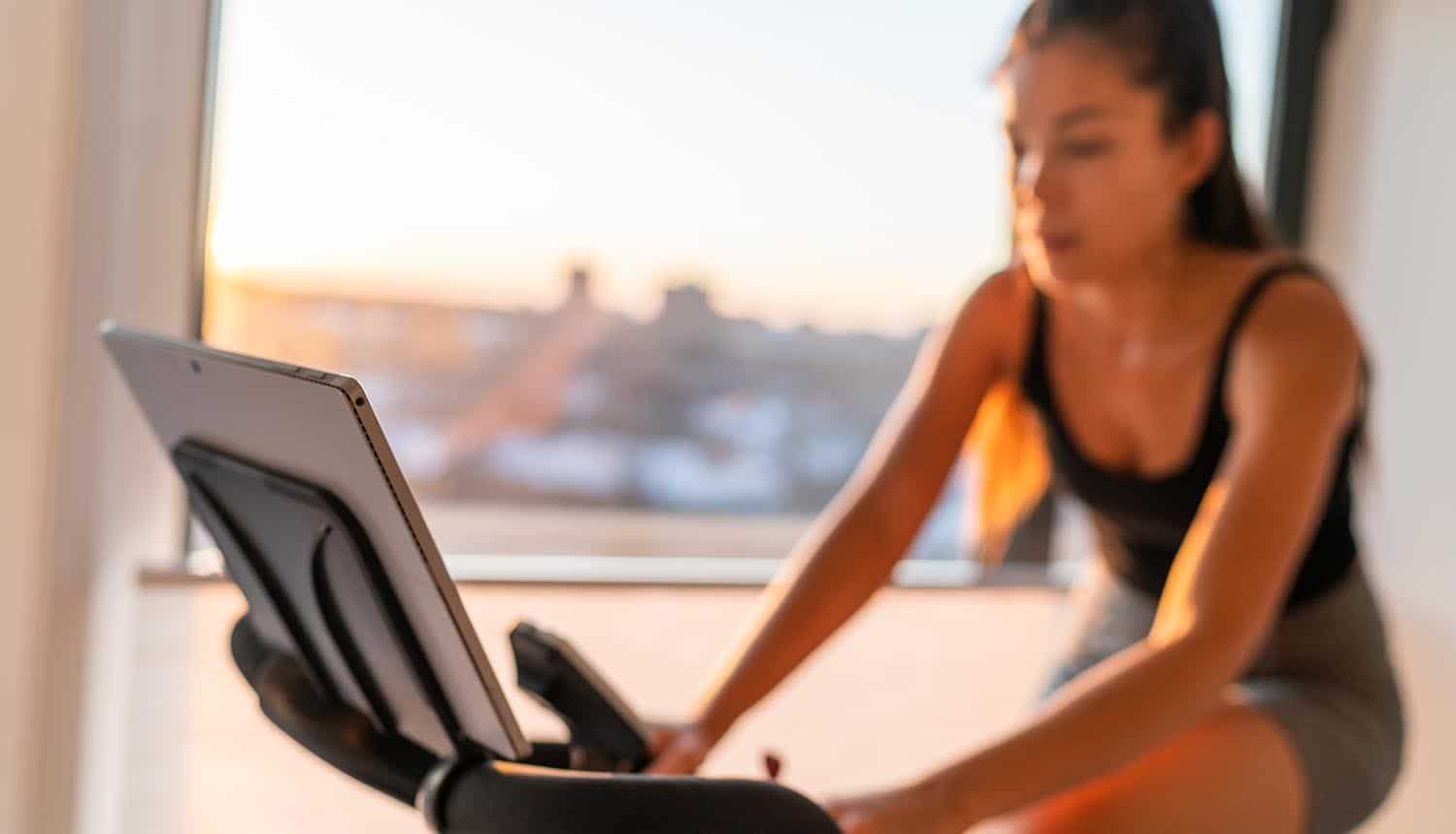 Woman exercising on smart stationary bike at home showing need for API security