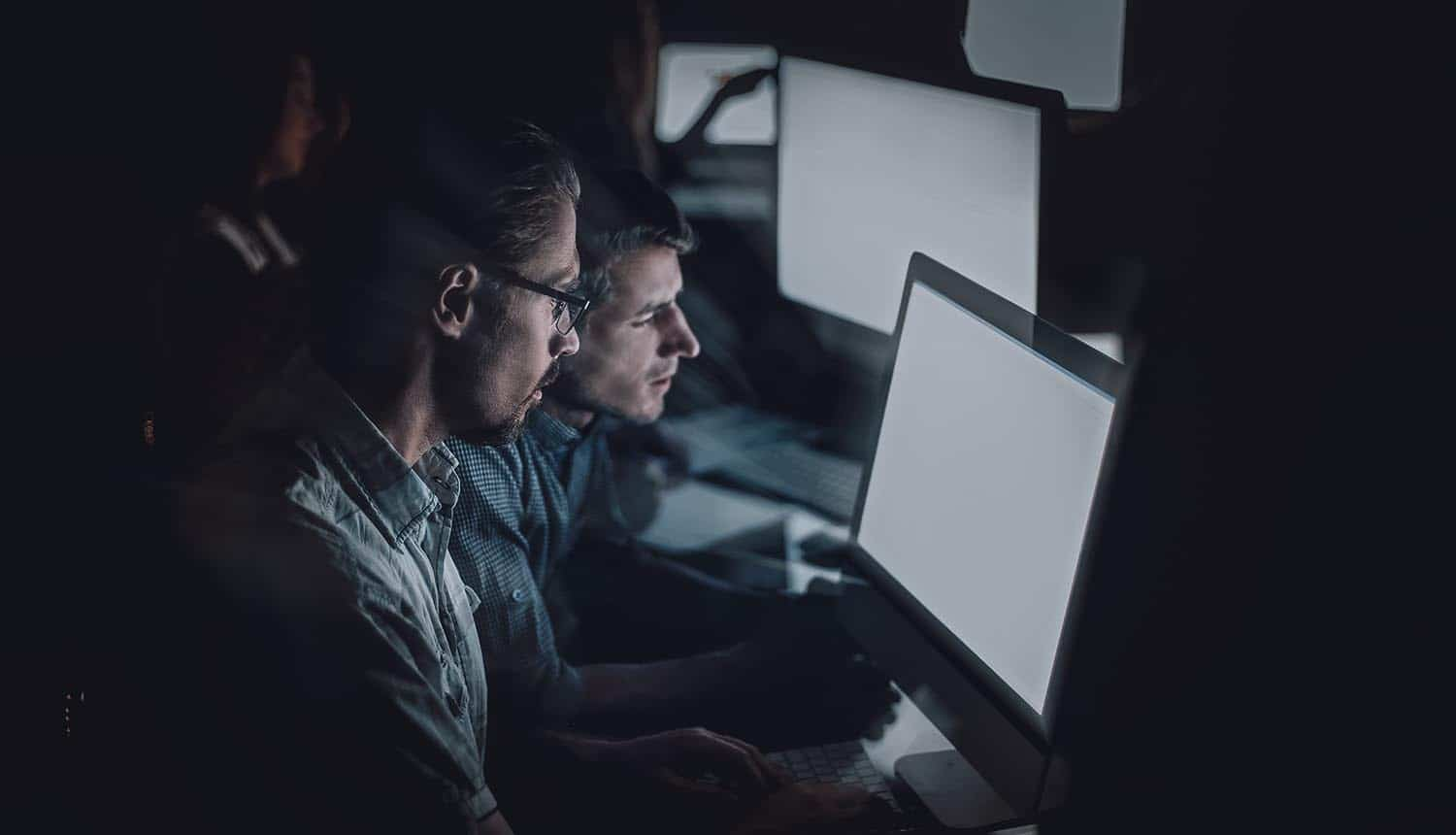 Dev team working on computers at night showing supply chain security