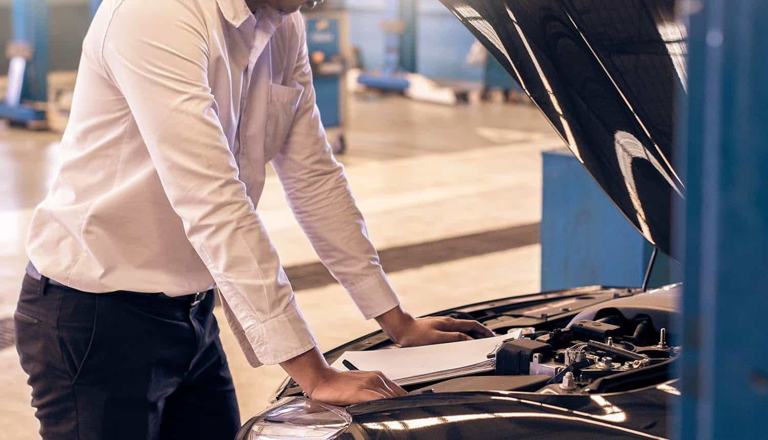 Man inspecting car showing need for vehicle cybersecurity