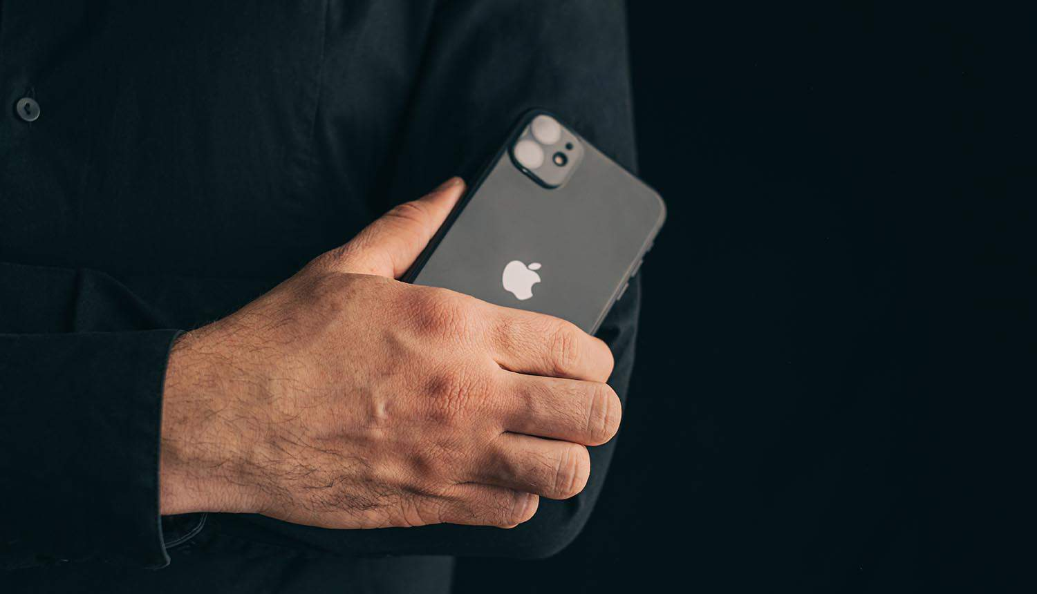 Businessman with folded arms cross his chest holding iPhone showing issues with phone data and iPhone repair
