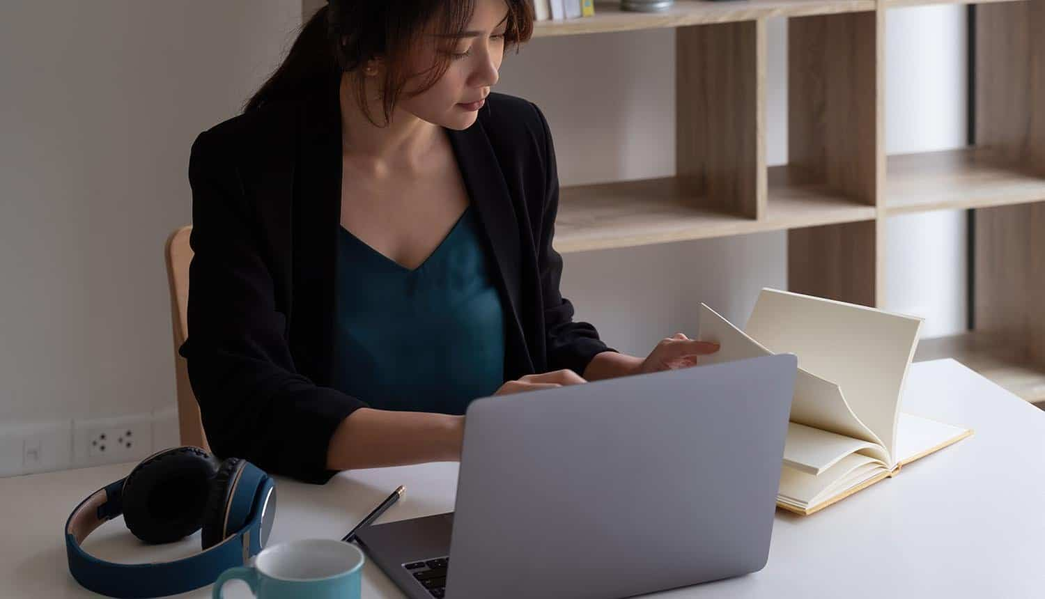 Woman using laptop for remote working showing employee behaviors in hybrid workplace