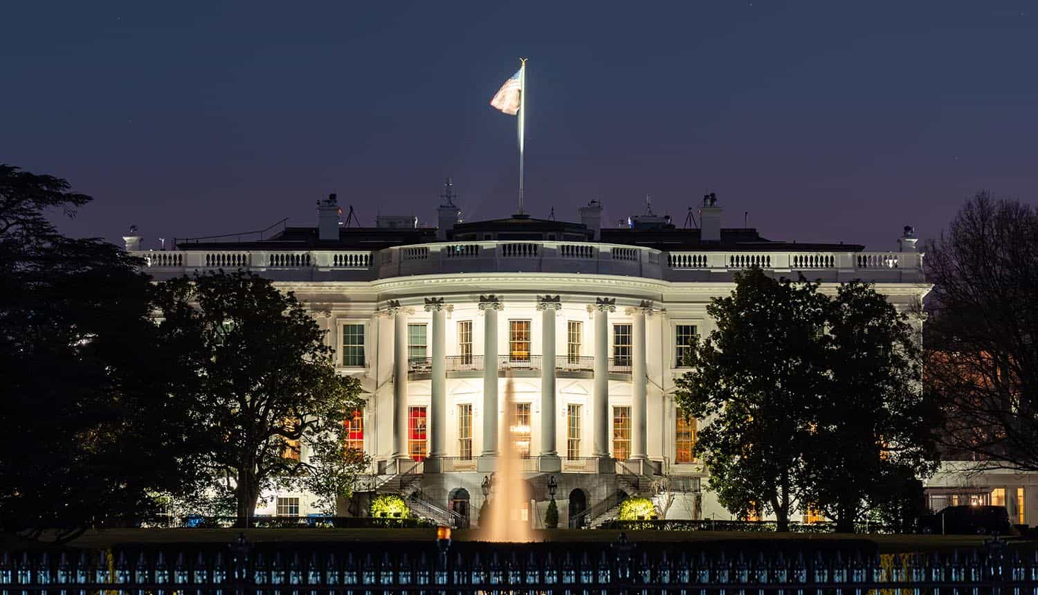 White House in Washington DC at night showing executive order to secure supply chain security and government contractors
