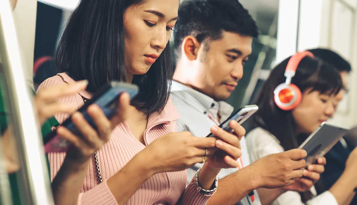 Young people using mobile phone in public underground train showing data breach by digital ad industry