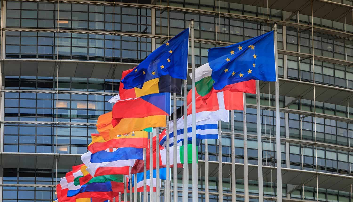 Set of European flags in front of the European Parliament on a winter day showing SCCs for data transfer agreements in compliance with GDPR
