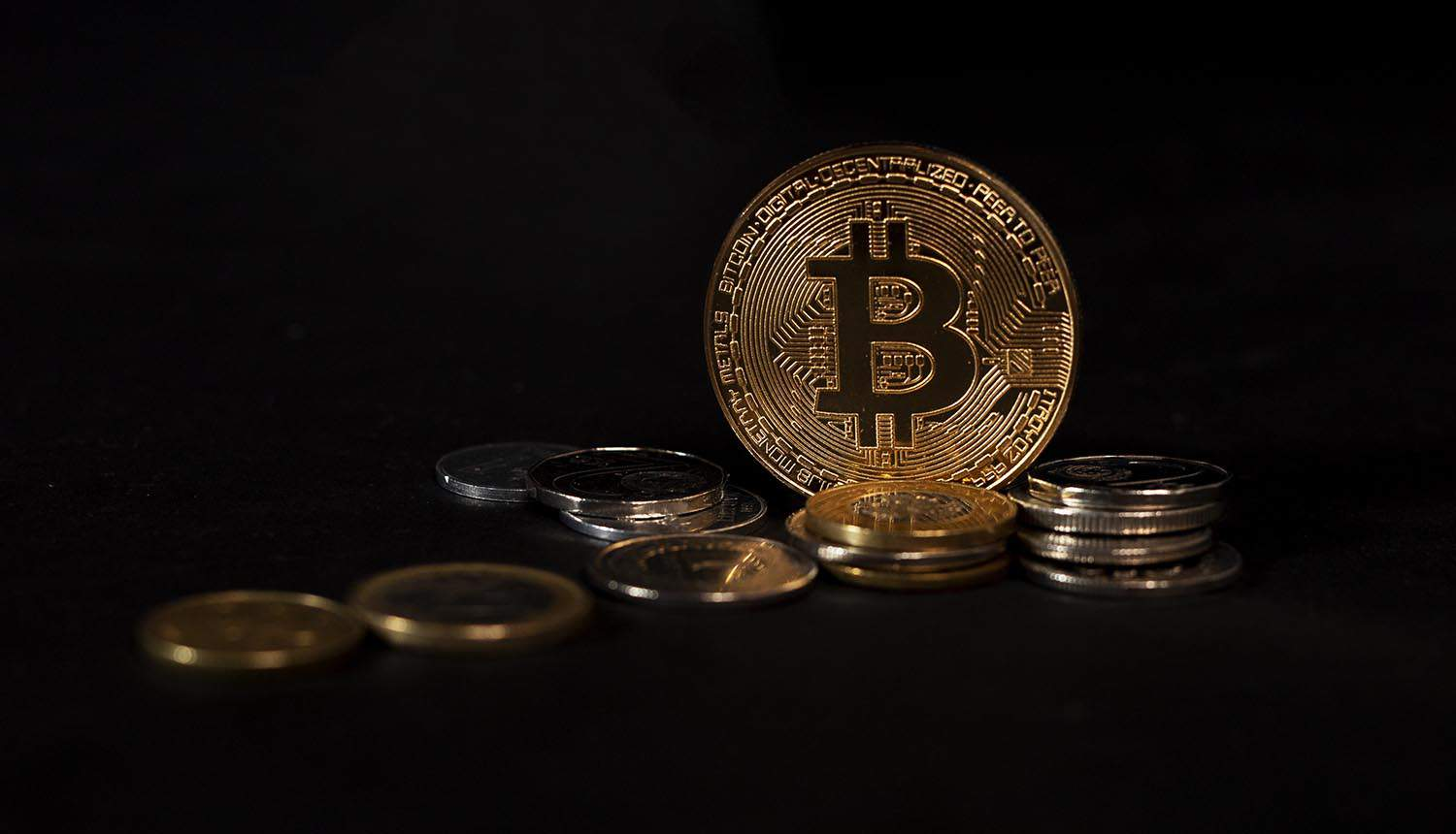 Bitcoin coin standing on other cryptocurrency showing recovery of ransomware payment