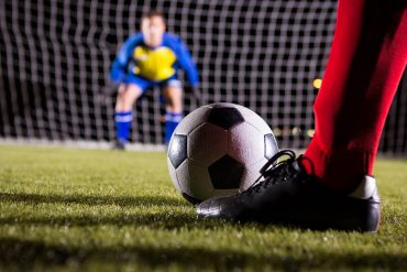 Low section of soccer player with ball against goalkeeper showing data breach and sale on hacking forum