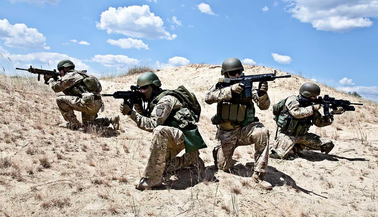 Squad of soldiers in the desert during military operation showing cyber attacks can trigger military response