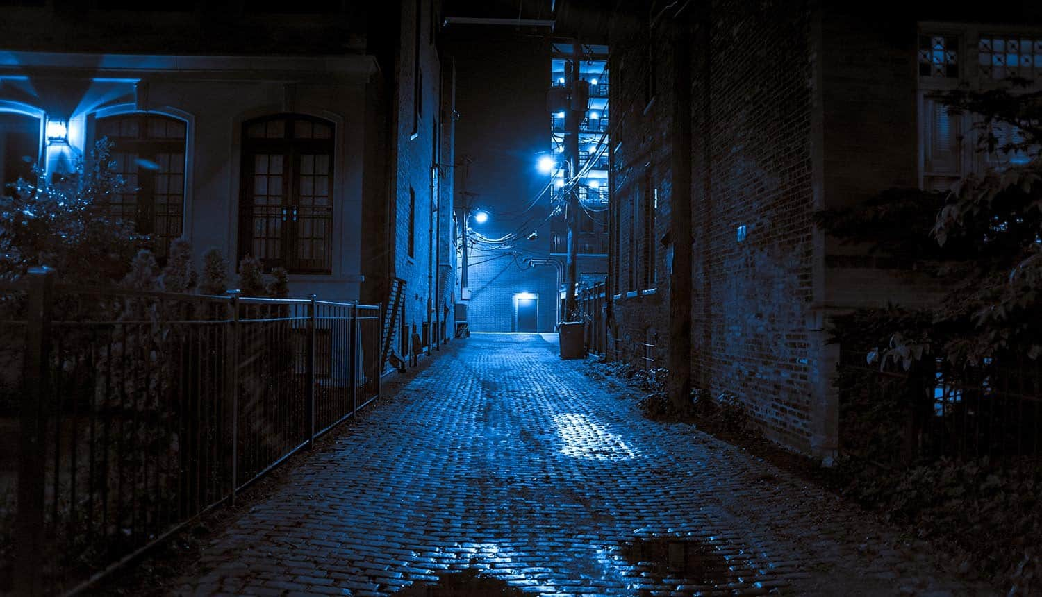 Dark and scary vintage cobblestone brick city alley at night showing darknet market cryptocurrency transactions