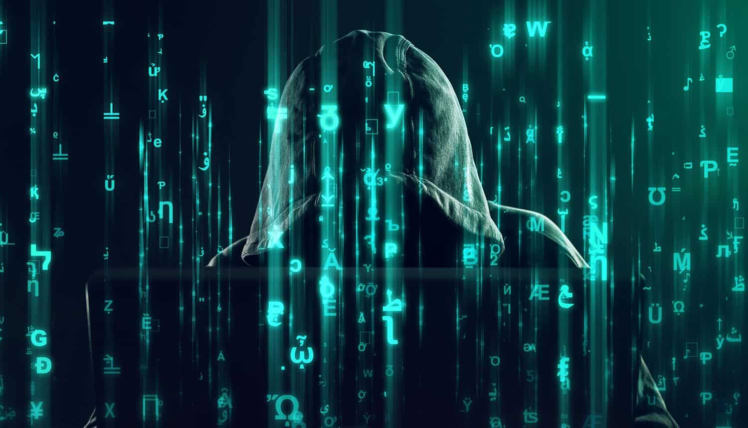 Hooded hacker working on laptop with code overlaying image showing ransomware attacks treated as terrorism