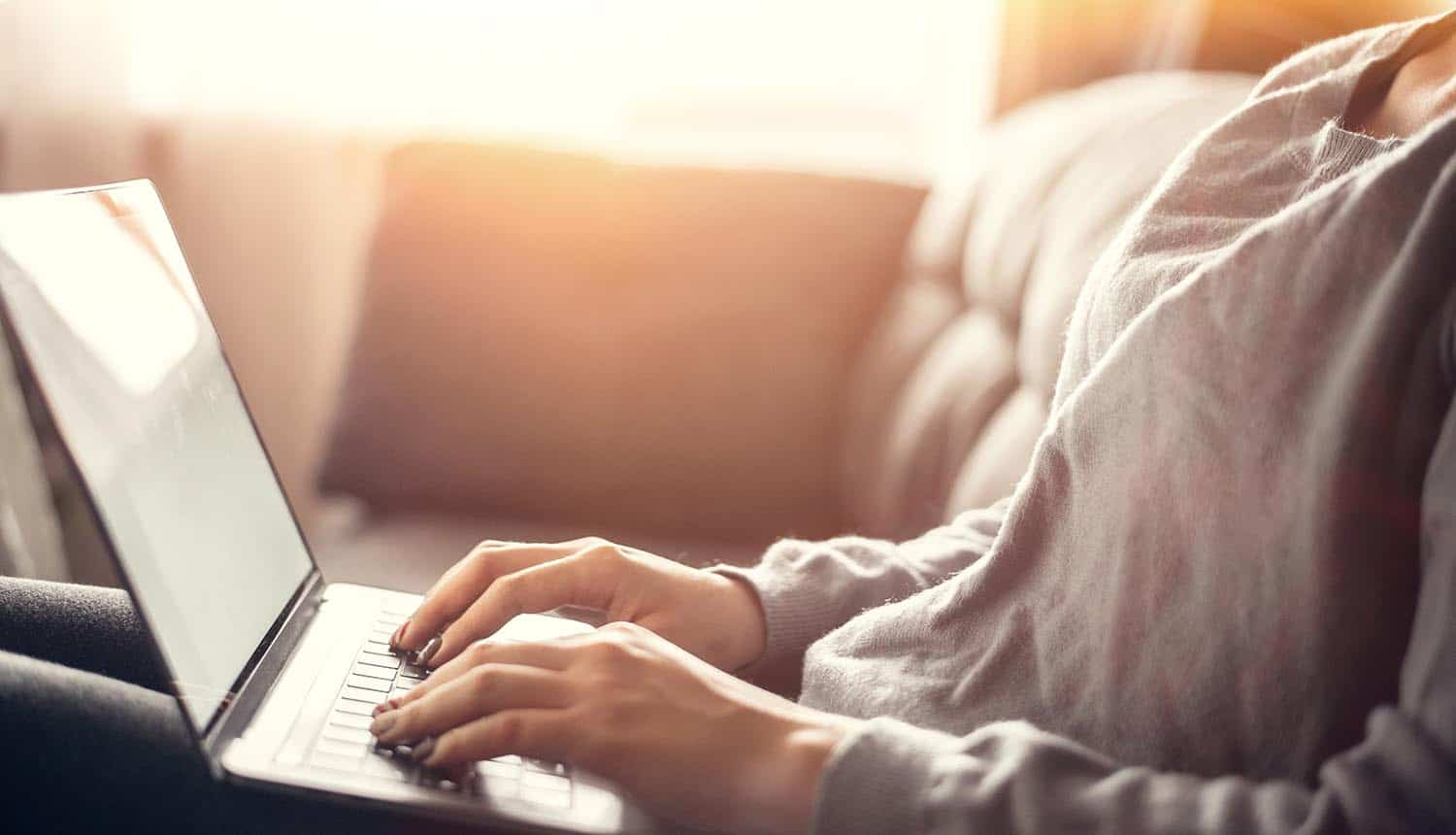 Woman working on laptop at home showing need for cybersecurity awareness