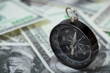 Closeup of a compass placed on U.S. Dollar banknotes showing rewards for information on ransomware attacks